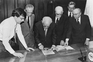 """Mark Hofmann watches as Mormon leaders inspect some of Hofmann's documents."" Special Collections Dept., J. Willard Marriott Library, University of Utah."